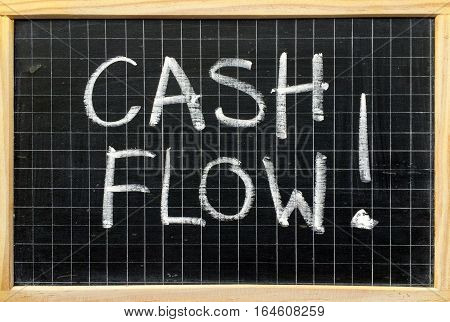 The words Cash Flow written in white chalk on a blackboard as a reminder for business to be aware of income and expenses