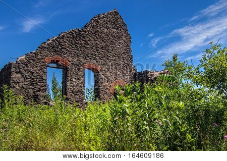 Abandoned Ghost Town Building. Exterior of a crumbling sandstone building reminiscent of a wild west ghost town. The building is located on a an abandoned mine site in the Keweenaw National Historic Park in Calumet, Michigan.