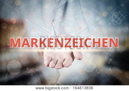Man Hand Holding Trademarks (in German) Text On Blurry Home Icon Property Background.