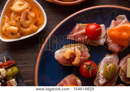 Top view of variety of mediterranean starters - spanish tapas with ham prawns and olives