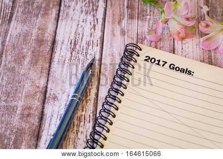 2017 Goals motivational concept with notebook and pen on wooden board