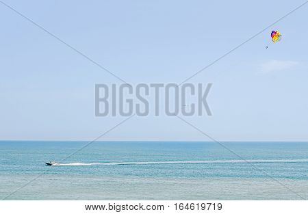 Colored Parasail Wing In The Blue Sky, Parasailing Also Known As Parascending Or Parakiting. Ship On