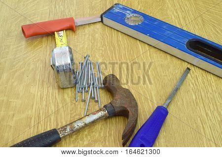 Hammer, nails, knife, ruler, spirit level and chisel on the table.