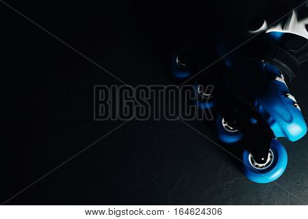 Close up view of blue roller skates inline skate or rollerblade on dark tinted grunge backgroung. Street culture, sports equipment