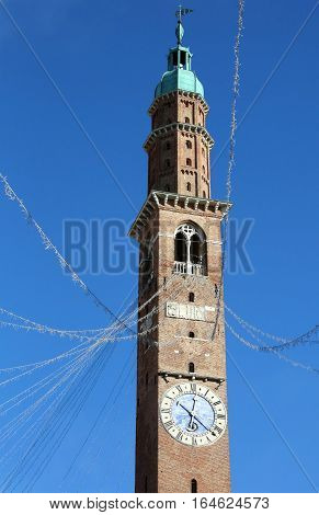 high bell tower of the historic building called BASILICA PALLADIANA in the city of Vicenza in Italy with christmas lights