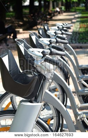 City bike rental. Row of many silver color bikes stands outdoor on sunny summer day closeup