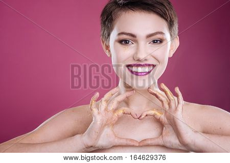 With love. Cheerful beautiufl womna smiling and expresing love while standing isolated on pink background