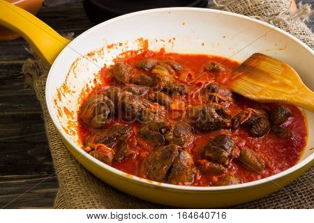 Fried chicken livers and hearts in tomato sauce in a frying pan