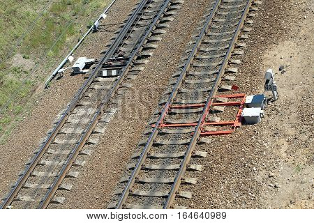 Railroad tracks on concrete sleepers, arrows and track equipment diagonal view