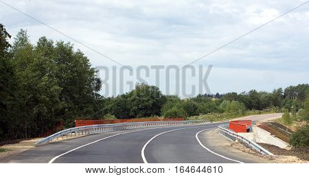 New bridge on country road with asphalt and orange fence to the sides