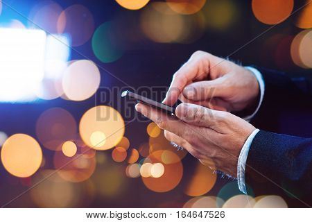 Businessman sending text message with mobile smart phone on city street at night