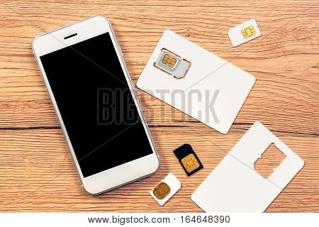 Smartphone with blank screen and SIM cards on the table top view