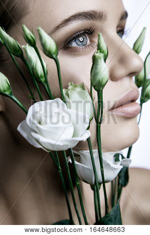 Calm Beauty Fashion Model Woman face. Portrait with white Rose flower. Beautiful Blonde Woman with blue eyes and Nude Makeup. studio shot.