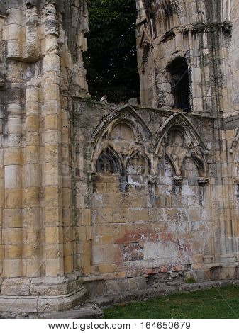 Medieval English ruins made from cut stone with arches and distinct coloring in Yorkshire England on a summer day.