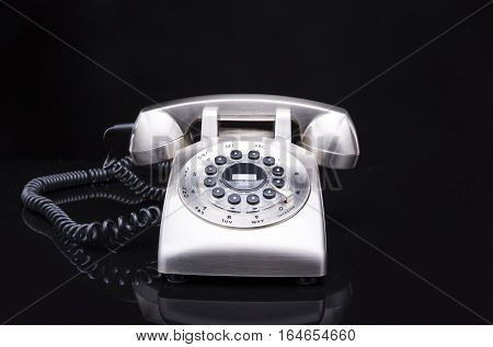 Metal, shiny retro telephone on a black background
