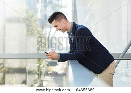 Smiling Young Business Man Standing With Smart Phone
