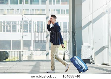 Business Casual Man Walking In Station With Phone And Suitcase