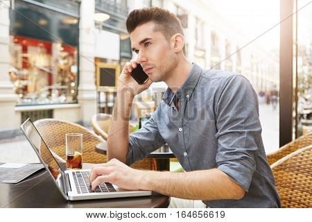 Man Sitting At Outside Restaurant With Drink Working With Laptop