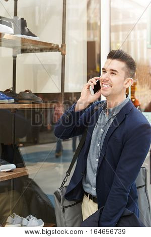 Handsome Man On Phone Call Outside Clothing Shop