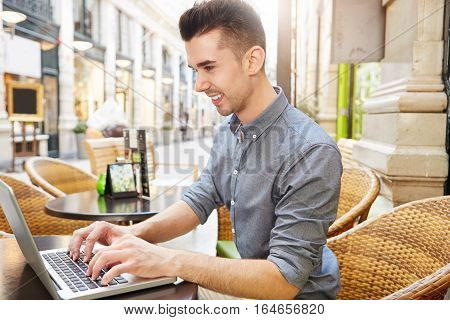 Side portrait of handsome happy man working at cafe typing on laptop