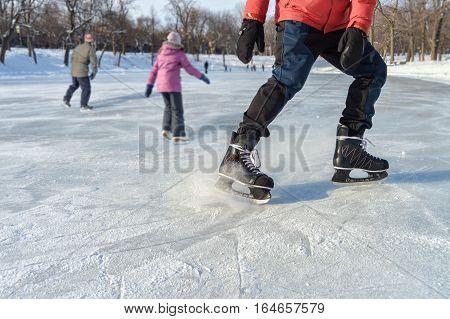 Close-up of ice skater braking on ice rink