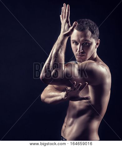 Young handsome man practicing martial arts on a black background