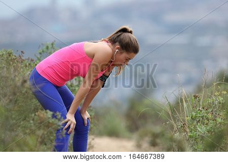 Side view of an exhausted runner wearing colorful sportswear resting in after run
