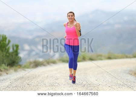 Front view of a runner girl wearing colorful sportswear running towards camera outdoors in the country