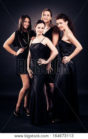 4 elegant ladies, aged between approx. 20 and approx. 40 , wearing black evening dresses