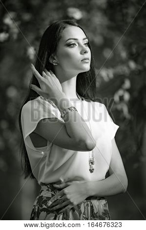 Beautiful yong model wearing luxury jewelry in spring garden. Black and white photography