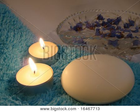 Essentials for a relaxing Spa ? soap, candles and flowers on blue towel