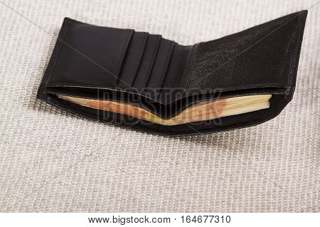 black leather men's wallet with money on a light background