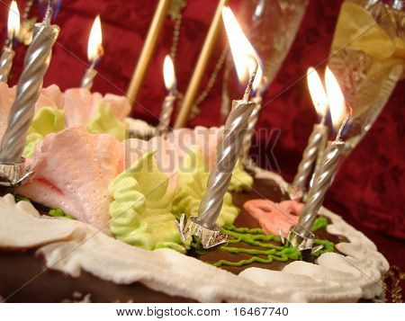 celebratory table (birthday cake and candles, two glasses with champagne) on red background