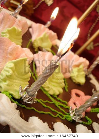 celebratory table (birthday cake and candles) on red background