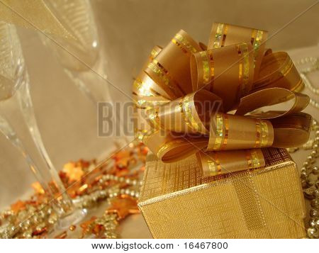 golden gift box on a beautiful background with champagne glasses