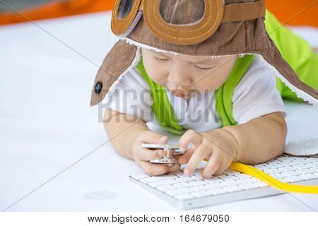 The Dream Of An Infant Concept, Baby Boy Wear A Pilot Hat And Playing A Stethoscope Near Computer Ke