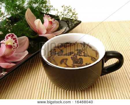 cup of tea with pink orchids on black plate over straw matt