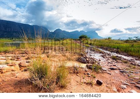 Dirt and rocky road on shallow river bed in Entabeni, South Africa safari game reserve