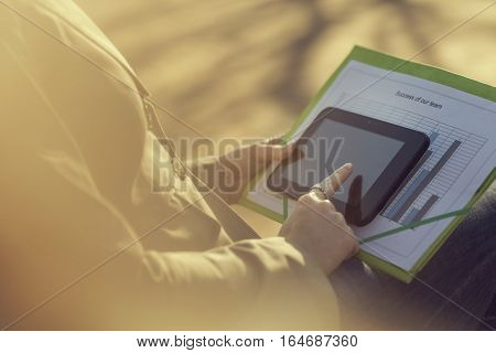 Business woman sitting on a bench in a park, holding a tablet computer and a folder with charts and graphs and working while on a break