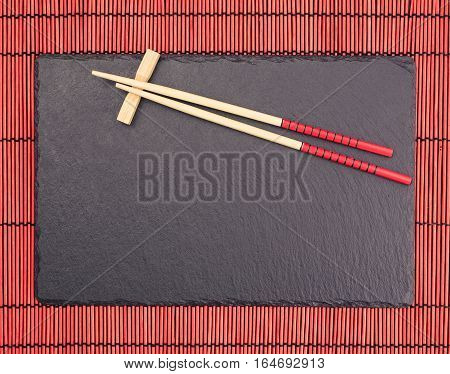 Chopsticks on black slate coaster on red bamboo scroll mat. Japanese style food background.  Top view with copy space