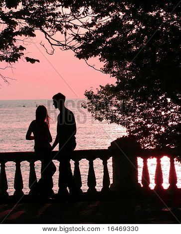 couple on the beach at pink sunset (sunrise)