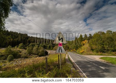 Dornoch Firth Scotland - June 3 2012: Road signs show on the left side the coming of a bottle neck and sharp turns. Set along the road in a wider green forested landscape under white clouds with blue patches.