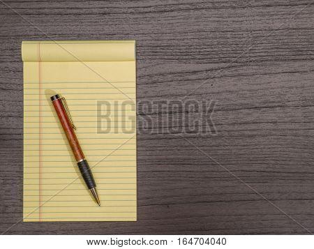 Dark Wood Desk Yellow Pad Pen on Pad