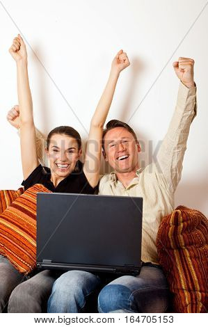 a couple is sitting on a couch and surfing the internet, probably buying something.