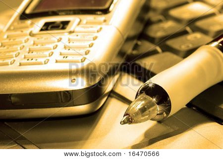 pen and mobile phone on computer keyboard in orange