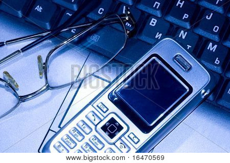 Mobile phone and glasses on computer keyboard (business conception)