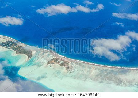 Aerial view of the island with clouds reef and lagoon. Island near Tahiti in the tropical archipelago of French Polynesia inside the Pacific ocean.