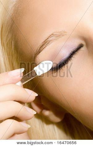 Nahaufnahme von jungen schönen Mädchen machen ihr Make-up mit Pinsel