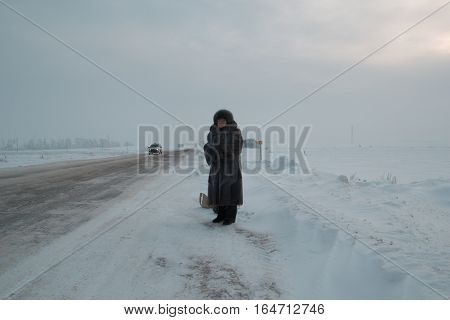 Portrait of senior woman fur coat and hat standing at winter snow covered field road, telephoto, wide angle