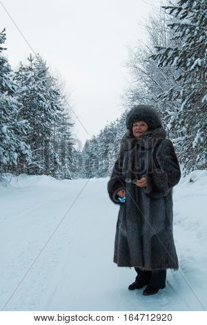Portrait of senior woman fur coat and hat standing in cold winter snow covered forest, vertical, wide angle